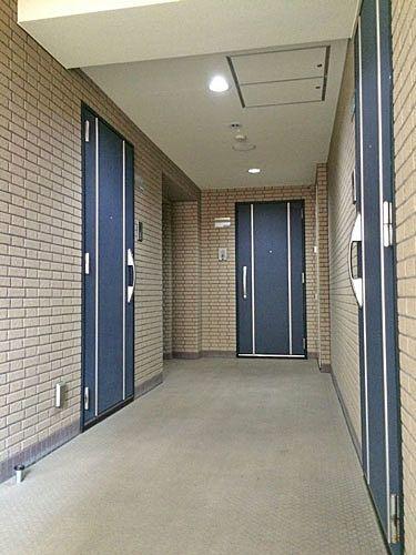 タイル張りの壁の共用廊下